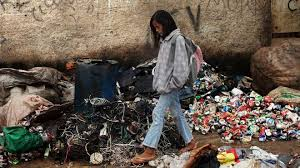 poverty_girl walking through dump